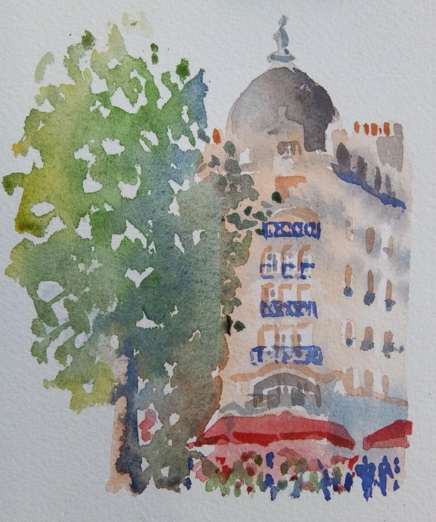 Immeuble d'angle, vu de face, surmonté d'une coupole. Café avec store rouge et foule colorée. A gauche, un arbre aussi haut que l'immeuble.