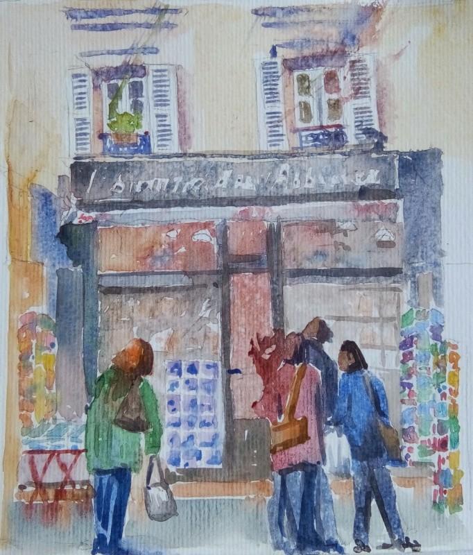 Quatre passants, de dos, devant une devanture de librairie au second plan. Au dessus, 2 fenêtres avec volets en bois ouvert.