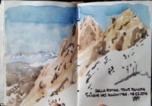 """A gauche, montagnes au premier plan sous le ciel bleu. Autres montagnes au loin à droite. Texte """"SELLA RONDA TOUR PANORAMIQUE DES DOLOMITES. 18.03.2016"""". Signé BR."""