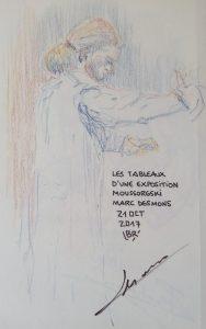"""Chef d'orchestre (homme) en train de diriger, vêtu d'une tunique avec autographe du sujet. Texte """"Les tableaux d'une exposition, Moussorgski, 21 OCT 2017"""" Signé BR"""