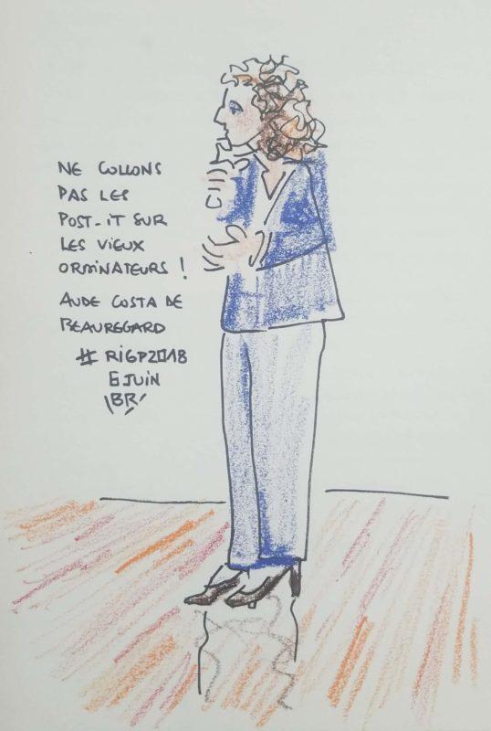 """Femme en pied tournée vers la gauche et parlant au micro, cheveux bouclés, costume-pantalon bleu foncé. Texte """"Ne collons pas les post-it sur les vieux ordinateurs ! Aude Costa de Beauregard #RIGP2018 6 juin"""" Signé BR"""